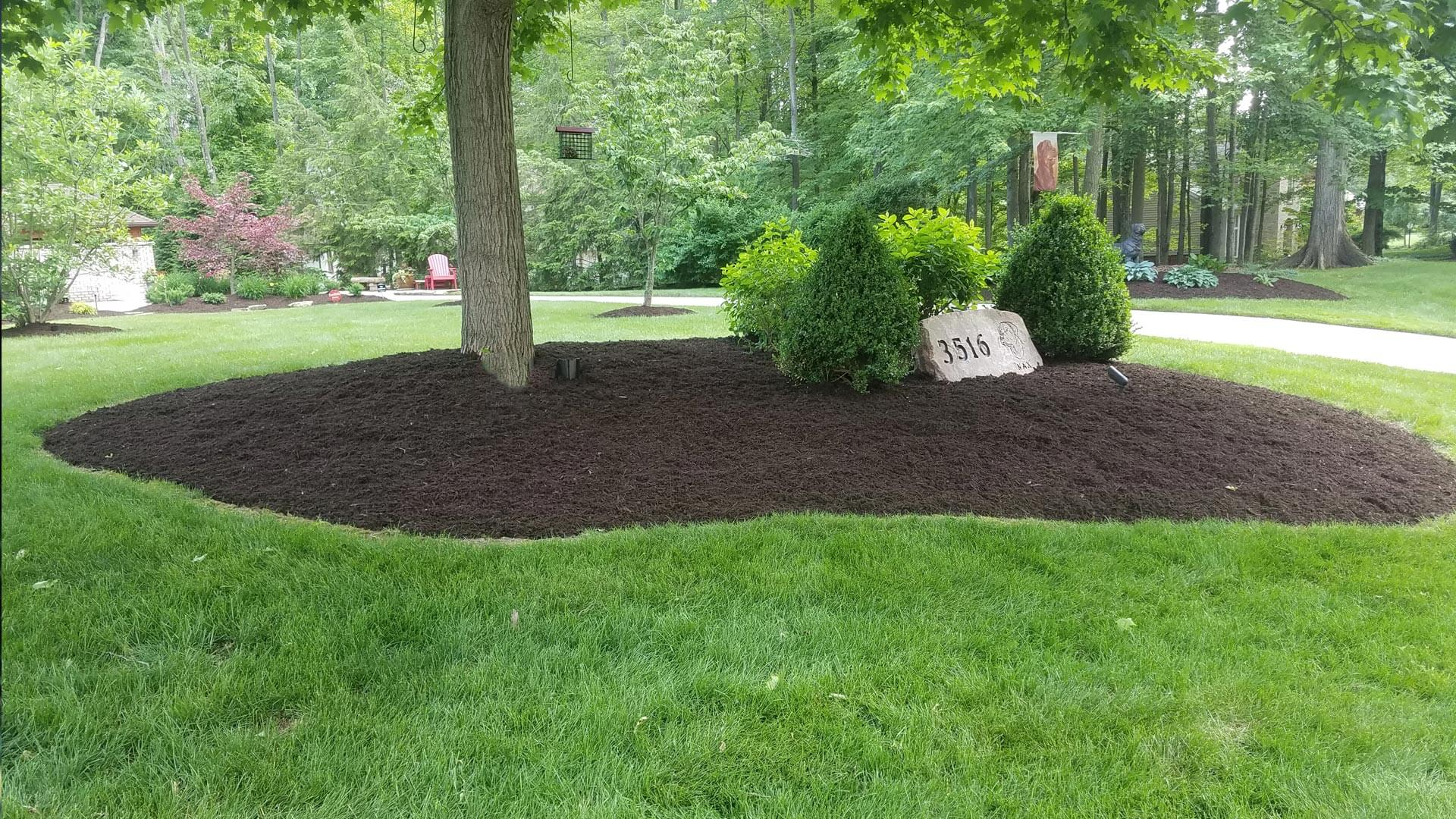 New landscaping bed installed with new mulch and a large rock focus point.